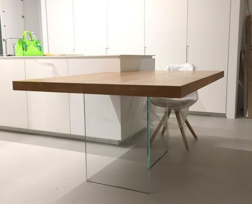 Tavolo composto da piano in legno di rovere naturale e sostegno in vetro temperato